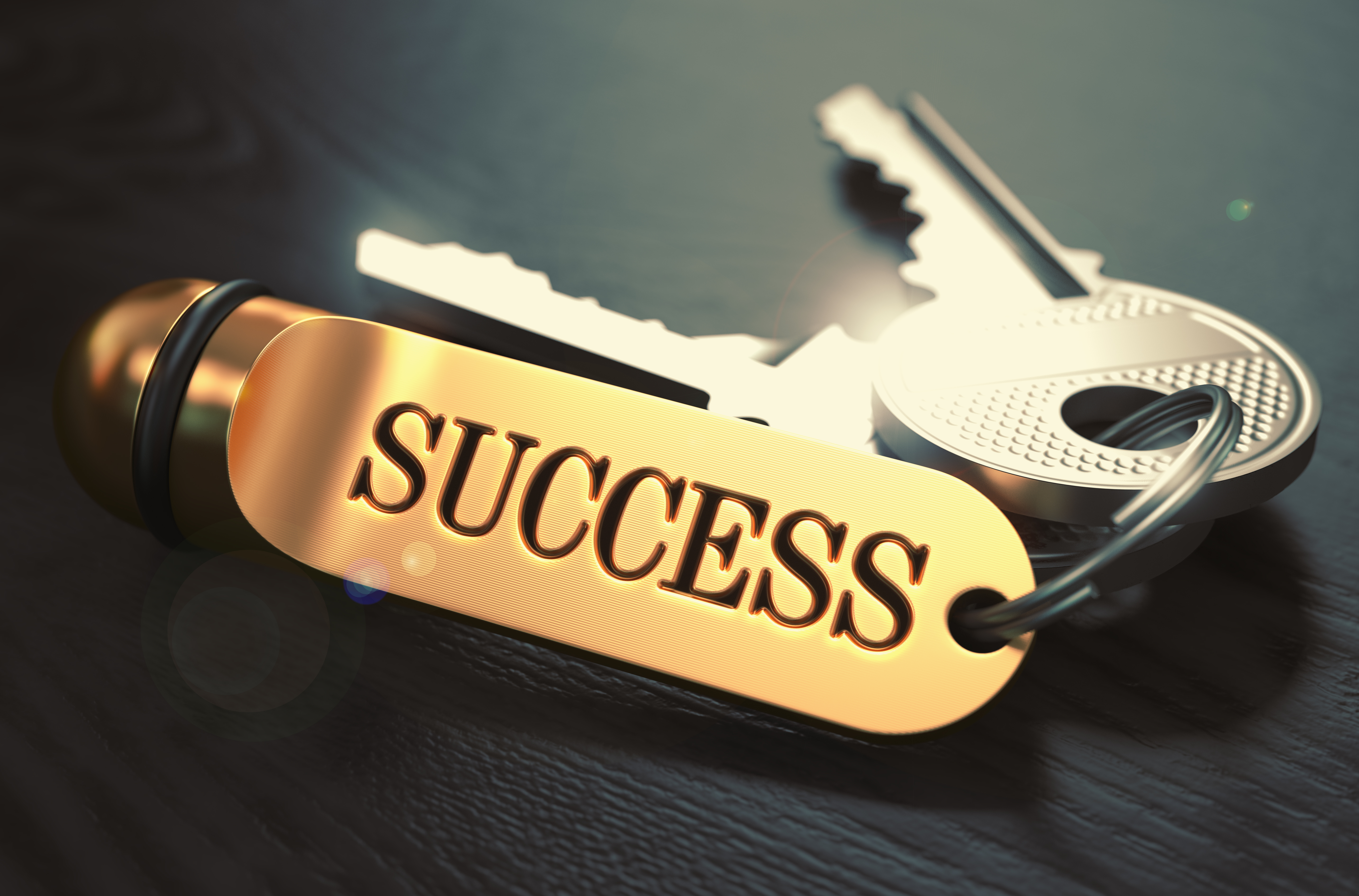 Keys to Success - Concept on Golden Keychain over Black Wooden Backgro